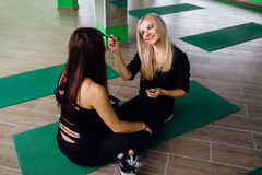 工作与美丽的少妇的专业化妆师 健身模型,航空瑜伽 坐在莲花坐 免版税库存照片