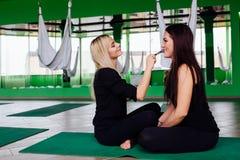 工作与美丽的少妇的专业化妆师 健身模型,航空瑜伽 坐在莲花坐 库存图片