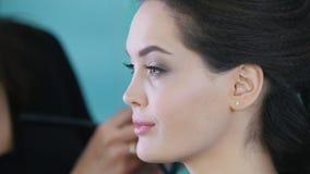 工作与美容院的客户的化妆师和美发师,应用眼影 股票录像