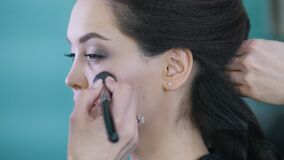工作与美容院的客户的化妆师和美发师,应用眼影 股票视频