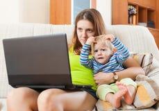 工作与膝上型计算机和婴孩的妇女 免版税库存图片
