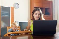 工作与膝上型计算机和婴孩的妇女 免版税图库摄影