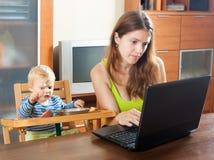 工作与膝上型计算机和婴孩的妇女 库存图片