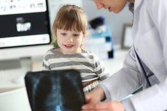 工作与逗人喜爱的女孩的女性儿科医生在她的办公室解释诊断 免版税库存图片
