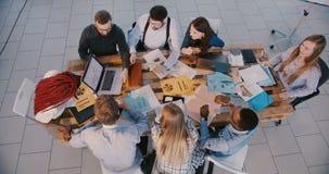工作与销售的数据一起的小组不同种族的专业商人在现代轻的办公室顶视图 股票视频