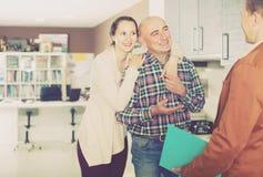 工作与顾客的努力售货员在商店 免版税图库摄影