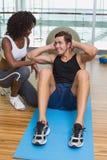 工作与锻炼席子的客户的个人教练员 图库摄影