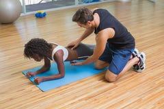 工作与锻炼席子的客户的个人教练员 免版税库存图片