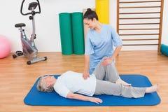 工作与锻炼席子的资深妇女的治疗师 库存照片