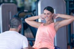 工作与他的健身房的客户的个人教练员 免版税图库摄影