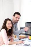 工作与他的在计算机上的工友的人 免版税图库摄影