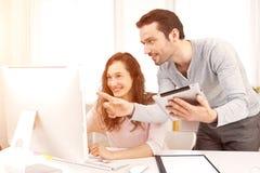 工作与他的在计算机上的工友的人 免版税库存图片