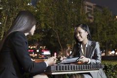 工作两名的女实业家,当吃晚餐时 免版税库存图片