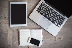 工作书桌顶视图有计算机和空白的笔记本的在木 免版税库存照片