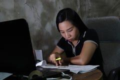 工作从家的亚裔妇女晚在恶劣的点燃的概念的夜班 黑暗的光有一些五谷和噪声 免版税库存图片