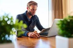 工作从家的现代贸易商在他的餐桌上 免版税库存照片