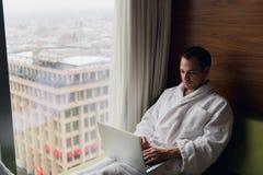 工作从膝上型计算机的家的年轻人自由职业者 库存照片