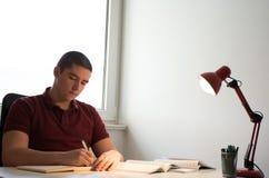 工作他的在书桌上的学生家庭作业 库存照片