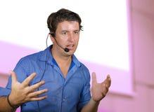 工作作为诱导报告人和业务管理教练的成功的人谈话与观众在会议室使用耳机 免版税库存图片