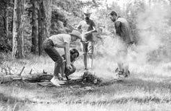 工作作为队的朋友保留篝火 公司野营的森林篝火为野餐做准备 增加一些木头射击 免版税库存照片