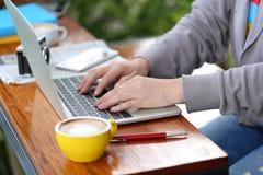 工作使用在coffe的手提电脑的自由职业者的年轻女人 免版税图库摄影