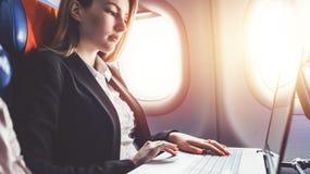 工作使用膝上型计算机的妇女,当旅行乘飞机时 库存图片