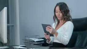 工作便携式计算机和数字式片剂的亚裔女商人在办公室 库存照片