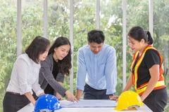 工作候选会议地点的小组工程师在办公室 队工作者谈建筑计划 电工木匠或 免版税库存图片