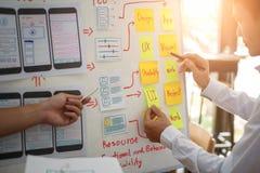 工作关于飞行的UX设计师创造性的小组与稠粘的笔记的流动应用计划 用户经验概念 库存照片