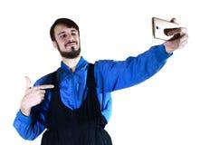 工作制服的一个年轻有胡子的人在一个现代智能手机做一selfie,指向他自己与他的手指 免版税图库摄影