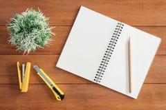 工作区书桌创造性的舱内甲板位置照片  与开放嘲笑的办公桌木桌背景笔记本和笔 免版税库存照片
