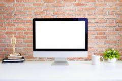 工作区在白色桌和砖墙上的计算机个人计算机 库存图片