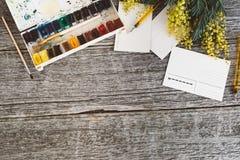 工作区 缠绕与含羞草、水彩、油漆刷和葡萄酒明信片的框架在木背景 免版税库存照片