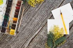 工作区 缠绕与含羞草、水彩、笔墨水和葡萄酒明信片的框架在木背景 笨人 免版税库存图片