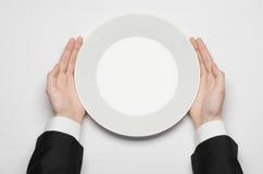 工作午餐和健康食物题材:在拿着一块白色空的板材的一套黑衣服的人的手和展示手指在isola打手势 免版税库存照片
