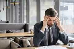 工作午餐的买卖人在坐在窗口附近的餐馆对顶头感觉负不适 免版税库存照片