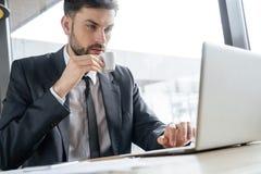 工作午餐的买卖人在坐在窗口饮用的浓咖啡浏览膝上型计算机附近的餐馆周道 免版税库存照片