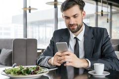 工作午餐的买卖人在坐的餐馆吃沙拉快乐浏览的智能手机 图库摄影