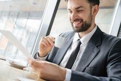 工作午餐的买卖人在快乐餐馆坐的饮用的浓咖啡读书的文件 免版税库存照片