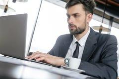 工作午餐的买卖人在运作在膝上型计算机特写镜头的餐馆坐的饮用的浓咖啡 免版税库存图片