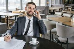 工作午餐的买卖人在采取笔记的餐馆坐的饮用的浓咖啡谈话在快乐的智能手机 库存照片