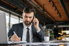 工作午餐的买卖人在餐馆坐的谈话在采取笔记的智能手机被集中 库存图片