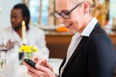 工作午餐的妇女检查在电话的邮件 库存图片