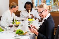 工作午餐的妇女检查在电话的邮件 免版税库存图片