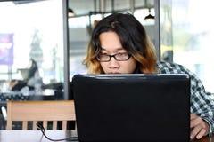 工作反对膝上型计算机的轻松的年轻亚裔行家人在他的办公室 免版税库存图片
