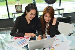 工作和使用膝上型计算机的亚裔女商人在会议室 免版税库存照片