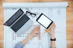 工作和做图纸的少妇建筑师 免版税库存照片