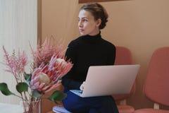 工作和写使用膝上型计算机的年轻女人或学生在膝盖 坐在咖啡馆在窗口附近,浪漫心情,温暖的颜色 免版税图库摄影