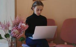 工作和写使用膝上型计算机的年轻女人或学生在膝盖 坐在咖啡馆在窗口附近,浪漫心情,温暖的颜色 库存照片