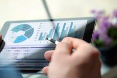 工作和分析在的商人财政图在一种片剂的图表在办公室 免版税库存照片